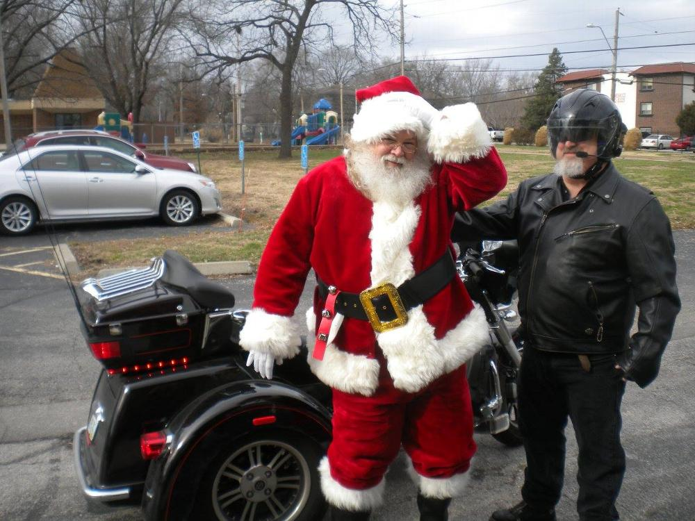 Santa straightens his hat after the ride on ER Pat Monks Harley