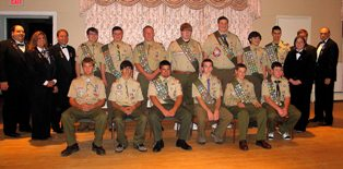 Pictured Above (L-R) with 13 of the 16 newest Eagle Scouts, are Taunton Lodge of Elks #150 Officers Paul Giannakoulis PER, Leading Knight, Sherry Davis Secretary and Lee Davis Exalted Ruler, Nicole Dudley Loyal Knight, Christopher Dudley Lecturing Knight and Joe Masterson, Past Lodge Trustee.