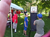 Kids playing with basketball hoop-shoot basket down at Owen Park during the parade.