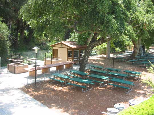 Grove picnic area with BBQ's serving table, refreshment stand, bandstand and dance floor.