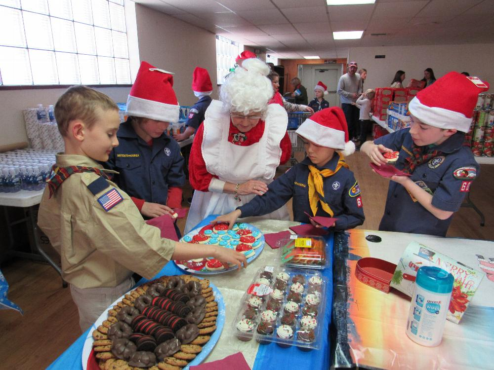 "Mrs Claus ( JR Latimer) and the Scouts in the cookie area of the ""Kids Corner"" of the Christmas Basket area. The Scouts helped with the basket distributions"