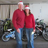 Christmas Basket Elves Kurt & LaRae helping with selection of bikes and sign up for kids to get helmets
