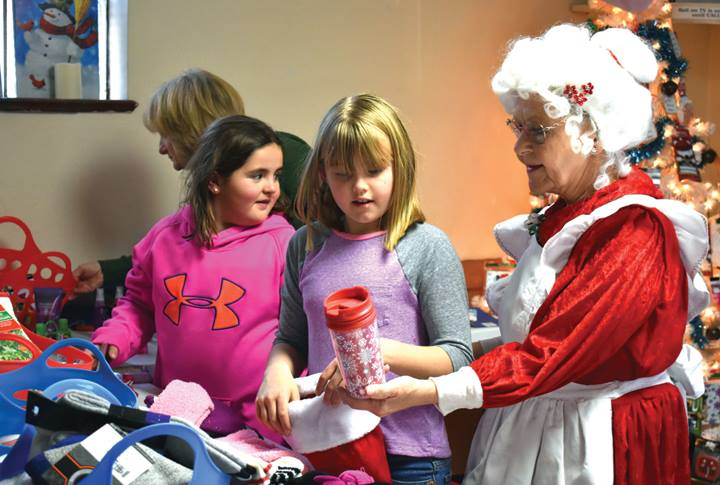 Photo in Mountain Mail Newspaper of kids with Mrs Claus helping select a gift for their parents or guardians in the kids corner