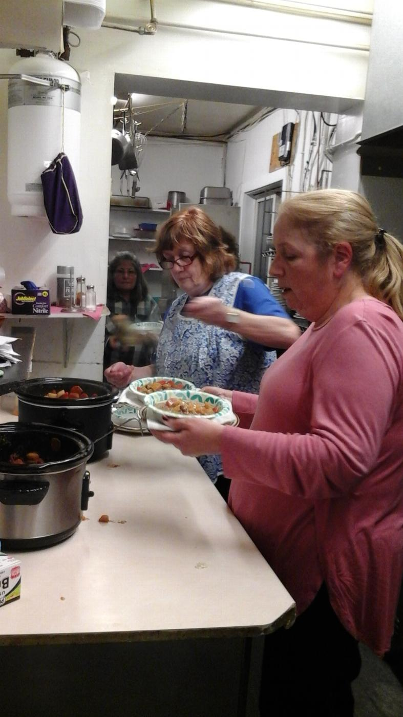 Exalted Ruler Becky Whelan and Chaplain Christa Donn dish up dinner for their guests.