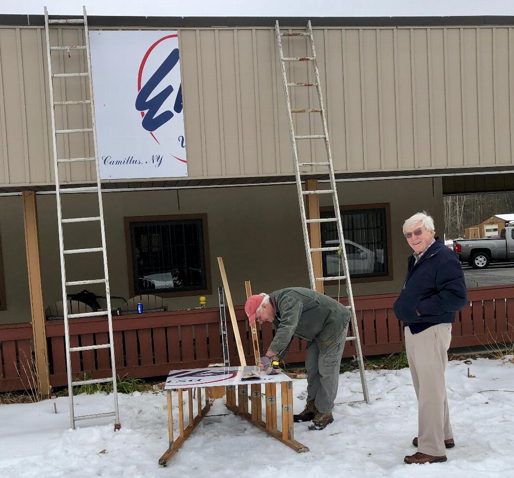 Rick Lopez works hard to place new Elks lodge sign on the building while Red Flaherty assists