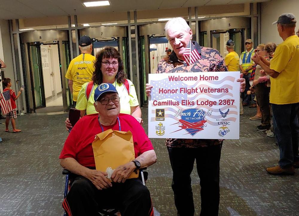 Trustee Stan Chesneski displays a Welcome Home sign during the 2019 Honor Flight return. The Lodge donated $1,500 provided by an ENF Gratitude Grant.