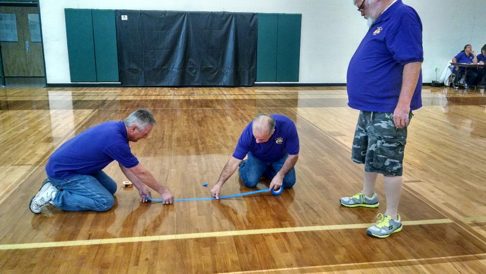 Brad Warwick, PER, Pete Gonzales, and Jim Prentice, PER measure out the lines for Hoop Shoot competitors.