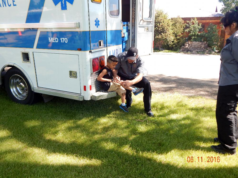 EMS helps put a band-aid on a little boy.