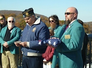 ER Jamie Depuy receives the Flag as American Legion Commander from Pleasant Valley NY recites the retirement ceremony.