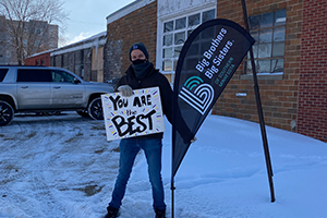 Elk volunteer holds up a sign reading 'You Are The Best.'