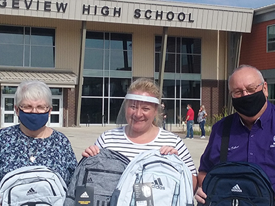 Elks in face masks hold up backpacks from their Gratitude Grant program.